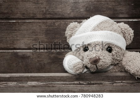 Teddy bear with bandages and broken hand on wood background in blackvand white,copy space, Stockfoto ©