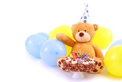 Teddy bear with birthday cap, balloons and cake with candles. Birthday greeting card, isolated, with copy space. Happy birthday cake with burning candles.