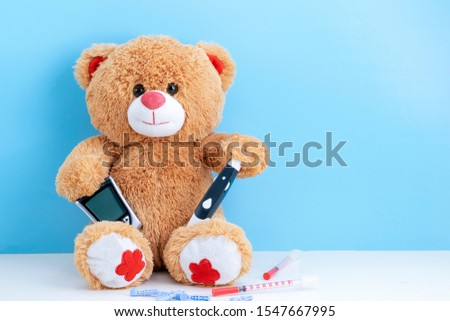 Teddy bear with blood sugar meter on blue background with space to copy; concept of diabetes in children; children's medicine; treatment of diabetes in children.