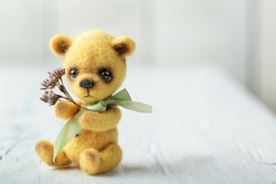 Teddy bear with bouquet of flowers on white wooden table. Space for copy