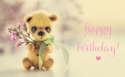 Teddy bear with flowers, text Happy Birthday. Greeting card, poster, background