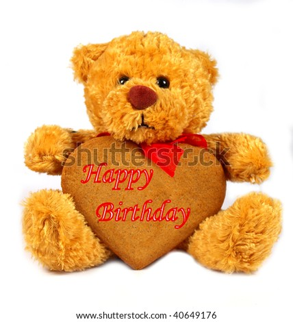 Teddy bear with gingerbread heart on white background