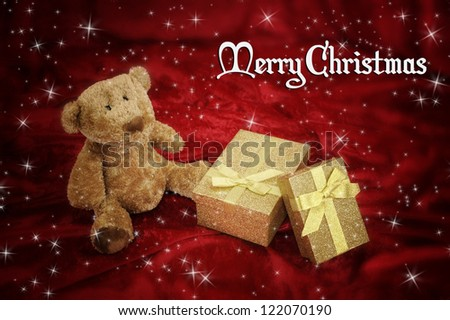 Teddy bear with golden gift box on red background