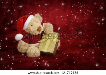 Teddy bear with golden gift box on red background with stars