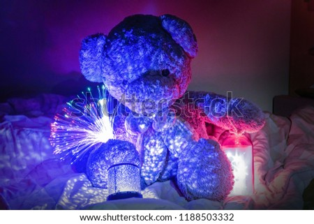 Teddy Bear with Ornamental lights and star lights in bed. Concept Christmas decoration. #1188503332