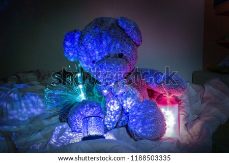 Teddy Bear with Ornamental lights and star lights in bed. Concept Christmas decoration. #1188503335