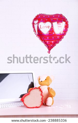 Teddy bear with present box and love heart balloon on wooden  computer table, on the brick wall background