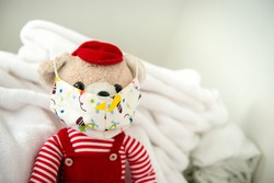 Teddy bear with protective medical mask on his face
