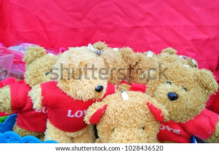 Teddy bear with red flower in the heart of Valentine's Day #1028436520