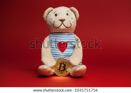 Teddy bear with red heart sewed on holding a bitcoin crypto currency token, isolated on red background, bear market concept  #1035751756