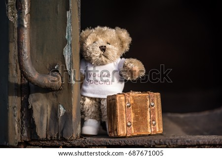 Teddy bear with suitcase says goodbye and goes on vacation by train. #687671005