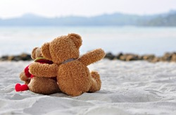 Teddy bears sitting on the beautiful beach with love. Concept about love and relationship
