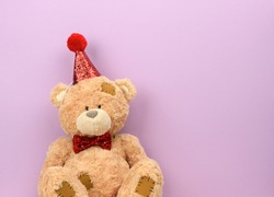 teddy beige bear in a red cap sits on a purple background, a place for an inscription