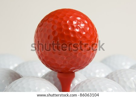 tee with a red ball of golf accompanied by white balls