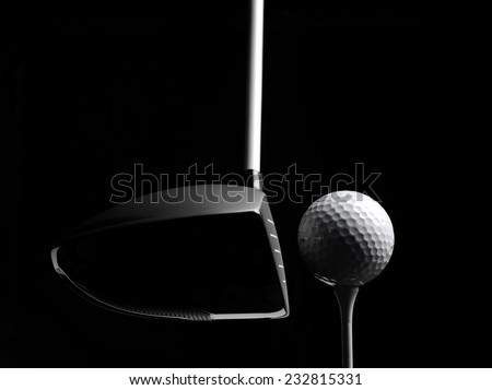 Teeing off in a game of golf with a golf ball and golf tee, isolated on black with copy space.