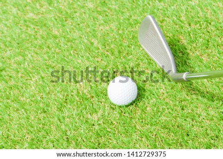 Teeing off with golf club and golf ball on green lawn