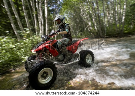 Teen aged girl riding quad through creek in the forest. Slow shutter speed for motion blur with focus on rider. Space for ad copy. Subject is slightly approaching camera. Stock photo ©