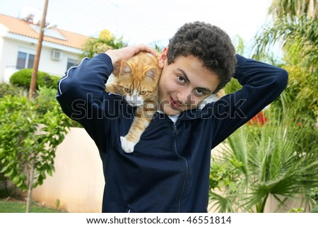 Teen and cat on his shoulders.
