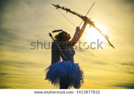 Teen angel. Teen angel girl archer on sunset. Silhouette of a cupid. Side view of teen girl archer against sunset