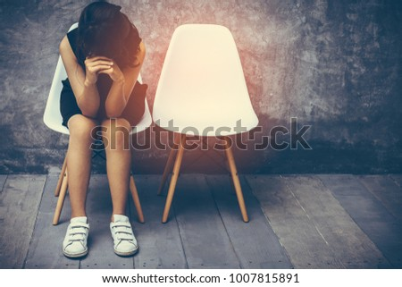 Teen asian pretty girl wearing black put your hands together sitting on a chair white In front of the meeting room was bare concrete wall Her face expressed sorrow and worry about the problem in life.