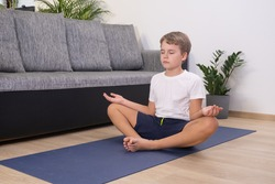 Teen blond boy exercising sport at home practice yoga sit in pose keep calm meditating Child physical activity Healhty lifestyle