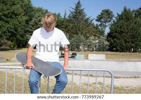teen blond boy sitting next to the bowl of the urban skatepark #773989267
