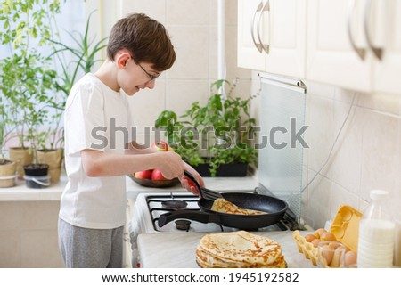 teen boy bakes (fries) pancakes in the kitchen. Cooking at home. Teenager boy is learning to cook. Kid boy 12 years old makes crepes by himself on frying pan. Independent child. Novice young chef