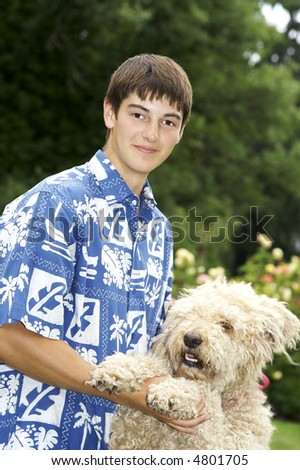 Teen boy dancing with his Golden Standard Poodle  Outside