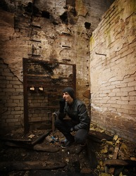 Teen boy dressed in black in an abandoned factory