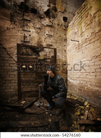 stock photo : Teen boy dressed in black in an abandoned factory