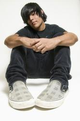 Teen boy dressed in black sitting on white background