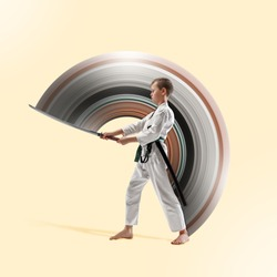 Teen boy fighting at Aikido training in martial arts school. Healthy lifestyle, movement, action, motion and sports concept. Fightrer in white kimono on yellow background. Karate man. Abstract design.
