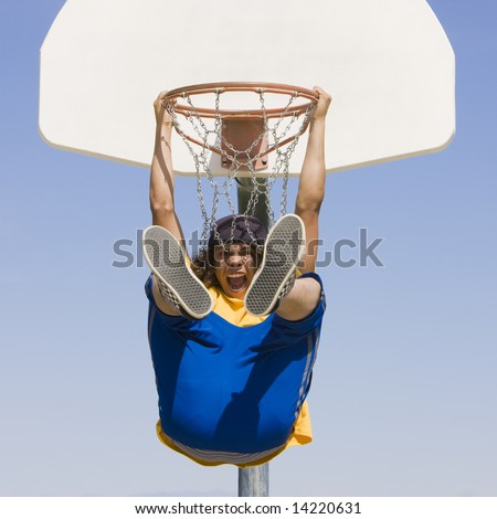 Teen boy hangs from a basketball hoop