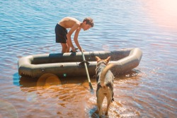 Teen boy in a rubber boat on the water with friend dog