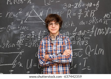 Teen Boy in glasses, blackboard filled with math formulas background
