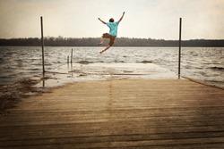 Teen Boy Jumping off a dock