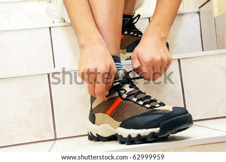teen boy on stairs tying his shoe closeup - stock photo