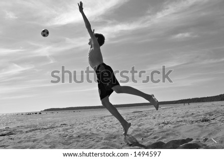 teen boy playing football on a beach, black and white photo