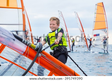 Teen boy raises windsurfing sail in the sea