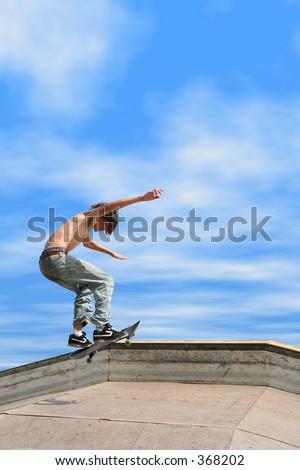 Teen boy shirtless in jeans skateboarding at outdoor skatepark.