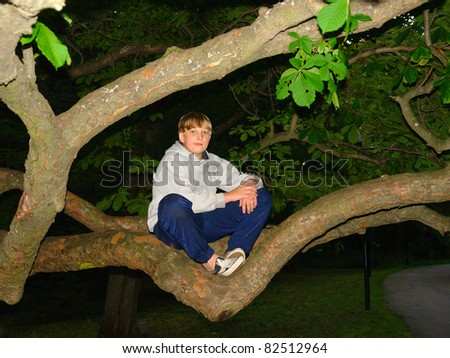 Teen boy sitting on the tree, night shot