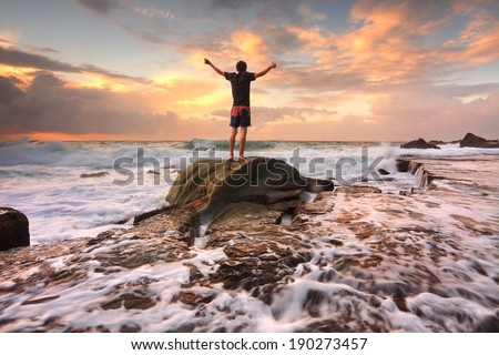 Teen boy stands on a rock among turbulent ocean seas at sunrise.  Worship, praise, zest, adventure, solitude, finding peace among lifes turbulent times.  Overcoming adversity.  Motion in water