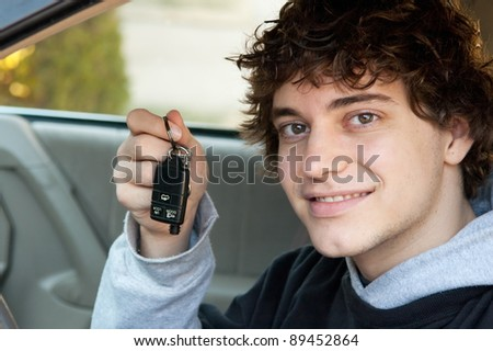 Teen boy who just got his driver's license holding keys in the car