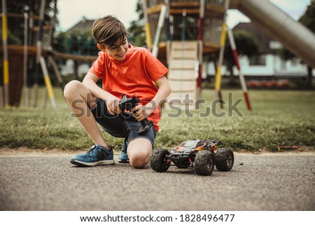 teen boy with electric remote control car toy play outdoor on sidewalk and have fun while enjoy his childhood Stock photo ©