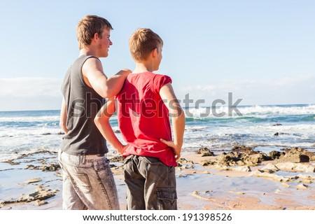 Teen Boys Beach Family Holiday Teen boys family together overlooking beach ocean water landscape