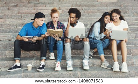 Teen communication. Group of young multiethnic friend sitting on stairs outdoor, sharing interesting information, panorama