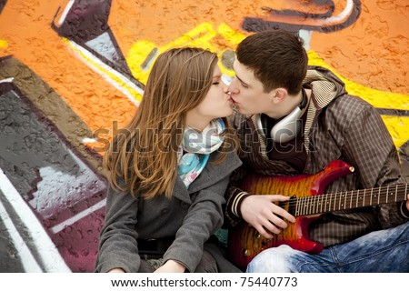Teen couple kissing at graffiti background.