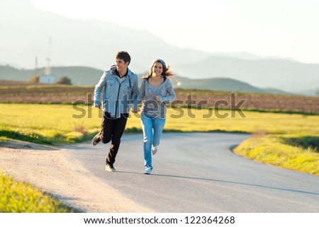 Teen couple running along road in countryside.