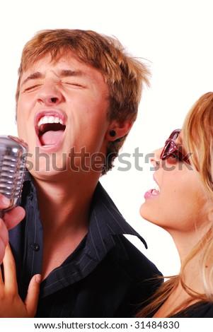 stock photo : Teen couple singing into retro microphone at karaoke