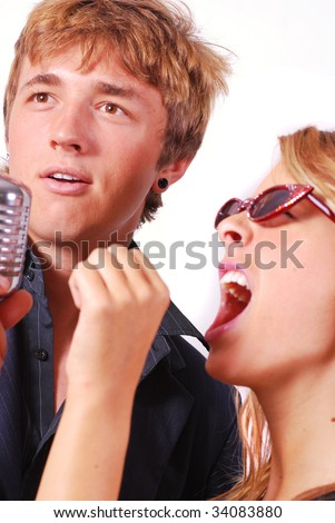 Teen couple singing into retro microphone at karaoke